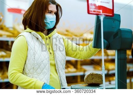 Customer Wearing Medical Mask And Gloves Weighing Rye Bread On Scales In Supermarket. Portrait Of Ho
