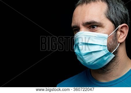 Man With A Medical Mask On Black Background With Copy Space For Text
