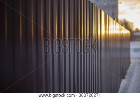 Metal Fence Around The Building. The Fence Around The Site. Wall Painted In Brown. Metal Constructio
