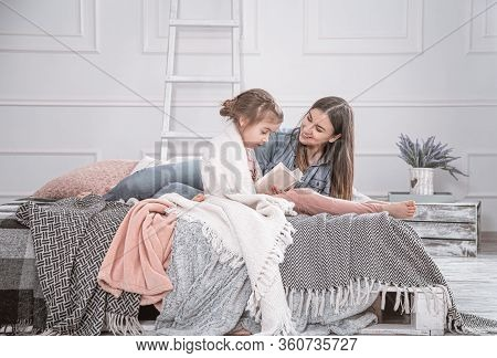 Happy Family. Mother And Daughter Reading A Book On The Bed.