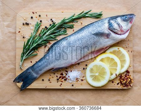 Raw Uncooked Sea Fish Preparation - Seabass Choice Of Fish On Cutting Board On The Parchment Paper.