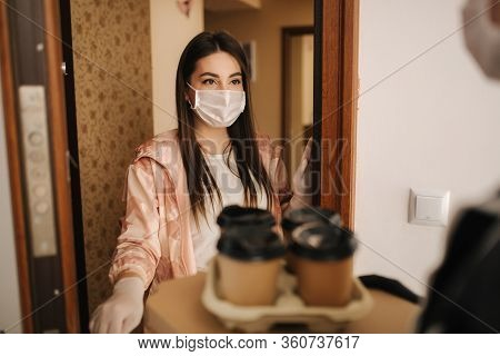 Man Delivery Pizza And Coffe To Customer In Mask And Gloves. Woman Open Door And Take Order. Coronav