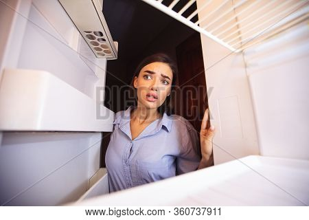 Young Shocked Woman Looking In Empty Fridge At Home, View From Inside