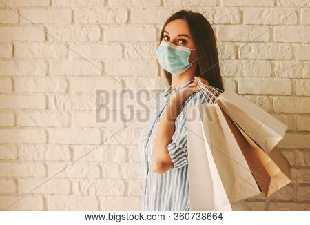 Beautiful Girl In Protective Face Mask Holding Shopping Bags In Hands. Young Woman Shopaholic In Med