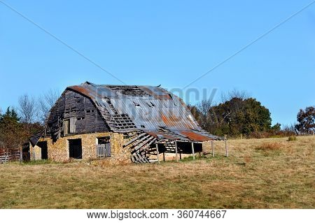 Derelict Stone Barn Is In Ruins.  Wooden Top Structure Is Caving In And Part Of The Tin On The Roof
