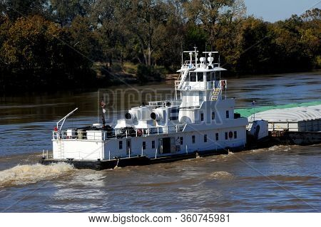 Tugboat, Also Called A Pusher, Muscles Its Way Up The Mississippi River In Arkansas.  Boat Is White.