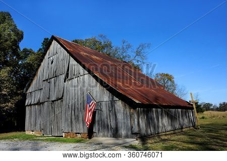 Wooden Cross Leans Against An Old Barn That Is Flying The American Flag.  Barn Is Weathered With Rus