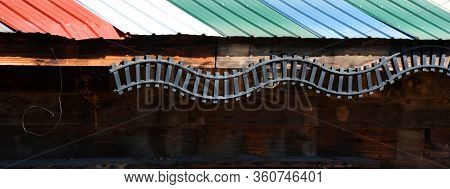 Railroad Buff Mounted An Incomplete Track On The Side Of His Wooden Shed.  Track Ends Rather Abrubtl