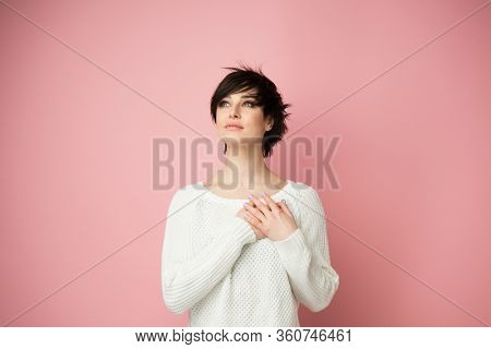 Young pretty girl smiling, looking up with hands on chest and grateful gesture on face. Happy woman feels grateful, hopes for successful plan realization, believes in success, wishes dream come true.
