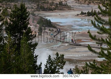 Yellowstone National Park, Usa - July 14 2014: A Group Of Tourists Walking On A Wooden Path Among Ge