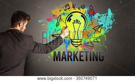 businessman drawing colorful light bulb with MARKETING inscription on textured concrete wall, new business idea concept