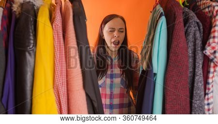 Close Up Of Young Woman Standing Between Clothes And Yawning From Pondering What To Choose Clothes I