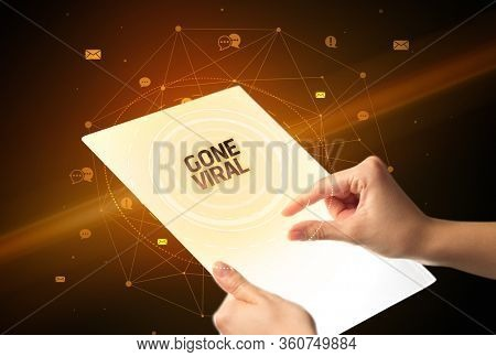 Holding futuristic tablet with GONE VIRAL inscription, social media concept