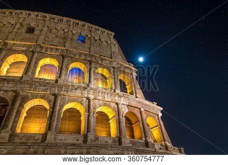 Roman Colosseum Illuminating At Night Under A Bright Full Moon And Starlight In Rome, Italy