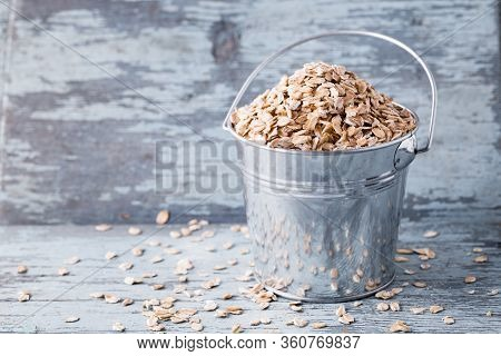 Raw Oat Flakes In A Bucket On Wooden Background.
