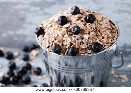 Oat Flakes With Blueberry In A Bucket On Wooden Background