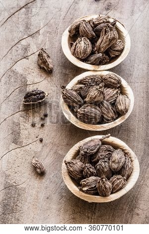 Three Bowls With Black Cardamom On Wooden Background
