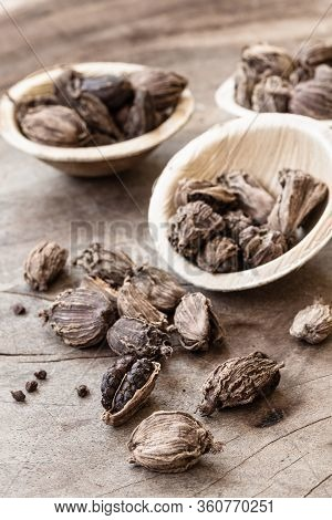 Black Cardamom Whole Seed In A Bowl On Wooden Background