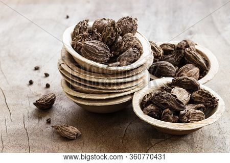 Black Cardamom In Bowls On Wooden Background
