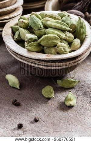 Whole Green Cardamom In A Bowl On Wooden Background