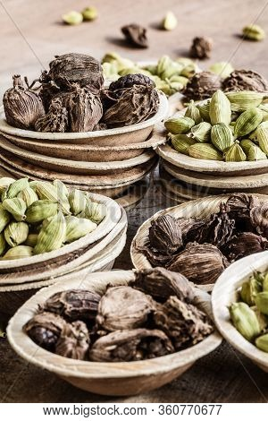 Black And Green Cardamom Whole Seed In Coconut Bowls On Wooden Background