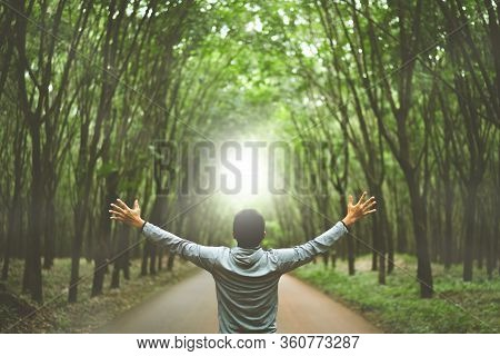 Man Raise Hand Up In Forrest With Sunlight Ray Abstract Background. Freedom Feel Good And Trave Holi