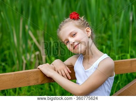Portrait Of Young Positive Girl In Park