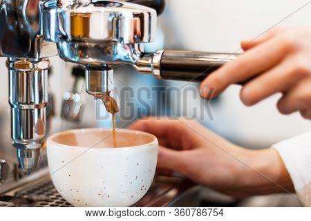 Process Of Preparing, Brewing White Cup Of Espresso, Americano. Closeup Female Barista Hands Are Mak