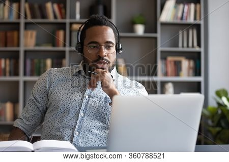 Focused Millennial Mixed Race Guy Consulting Clients Online.