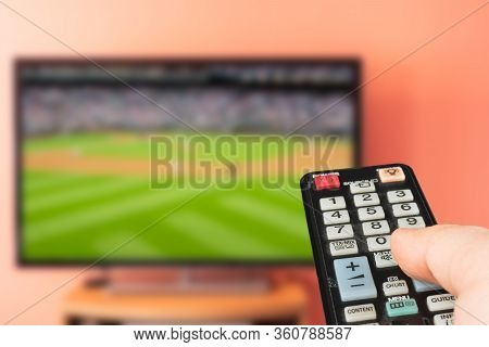 Caucasian Man Watching Baseball Game On Tv At Home. Changing Channels And Adjusting Volume With Tele