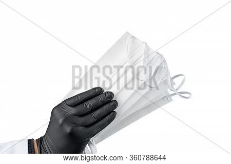 Hand In Black Protective Glove Holding Bunch Of Face Masks. Isolated On White Background.