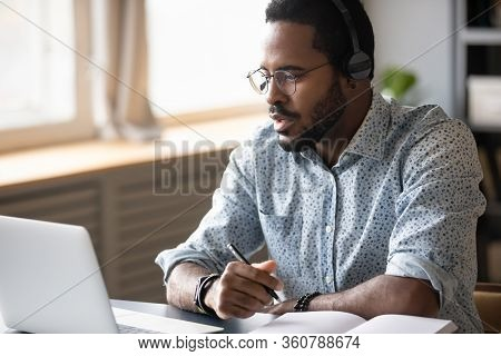 Focused Young African American Man Watching Educational Lecture Online.