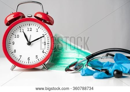 Red Clock, Green Protective Face Mask, Stethoscope And Gloves On A White Background. Copy Space In T