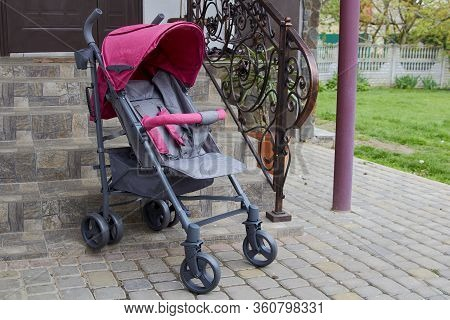 Empty Stroller In Front Of Stairs, In Front Of The House Is An Empty Baby Stroller For Outdoor Walks