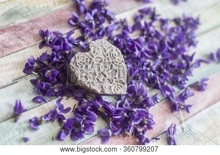 Organic Handmade Soap Shampoo On Purple Flowers Background. Picturesque Background With Violets.