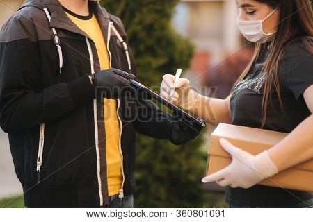 Man From Delivery Service In Medical Mask And Gloves Handing Fresh Food To Young Woman Customer Rece
