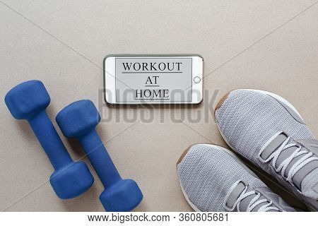 Flat Lay On A Light Background: Gray Sneakers, Blue Dumbbells And A Smartphone With The Inscription