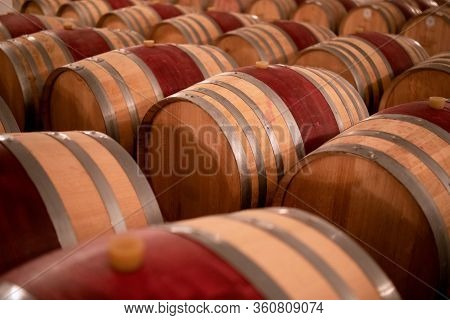 Wine Barrels Stacked In The Old Cellar Of The Winery. (selective Focus)