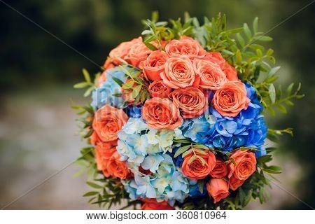 Orange And Blue Flower Arrangement For A Wedding: Orange Roses And Blue Larkspur.