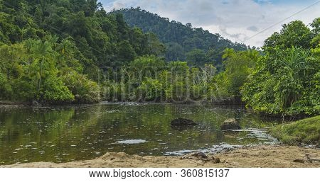 Pristine Vibrant Jungle River And Hills In Distance Seen In West Sumatra, Indonesia