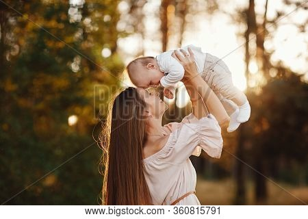 Young Mother Playing With Her Baby. Mom And Son Walking In A Park. Happy Mom Playing With Her Son. M