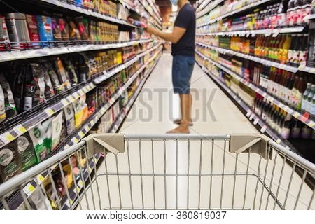 Shopping Cart In Super Market With Consumer In Protective Mask In Blur Background Coronavirus Concep