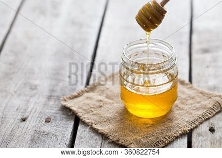 Honey With Wooden Honey Dipper On Wooden Table. Honey Background.