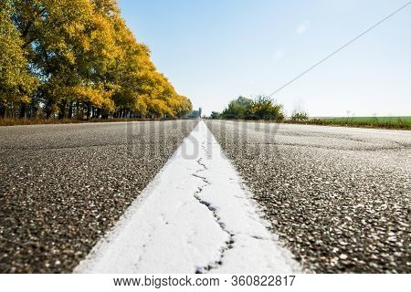 Old Asphalt Road. Driving On An Empty Road. Cracked White Line On The Asphalt Road. Shallow Depth Of