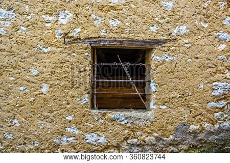Window With Disused Railing And Wooden Logs