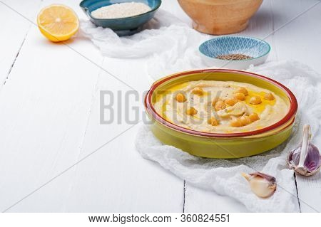 Bowl Of Arabic Or Lebanese Vegetarian Hummus.in Green Bowl On A White Wooden Background. Traditional