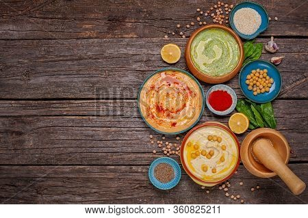 Colorful Hummus Bowls, Healthy Vegan Dips On A Brown Wooden Wooden Background. Hummus With Spinach,
