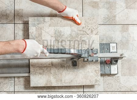 A Man Is Cutting A Ceramic Tile With A Tile Cutter.
