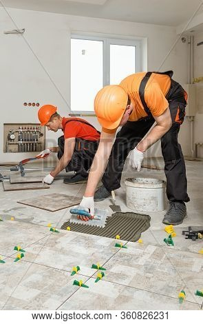 Two Workers Are Installing Ceramic Tiles On The Floor.