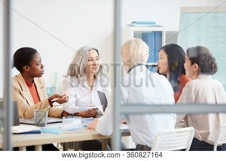 Portrait Of Diverse Female Business Team Discussing Project While Sitting At Table During Meeting In